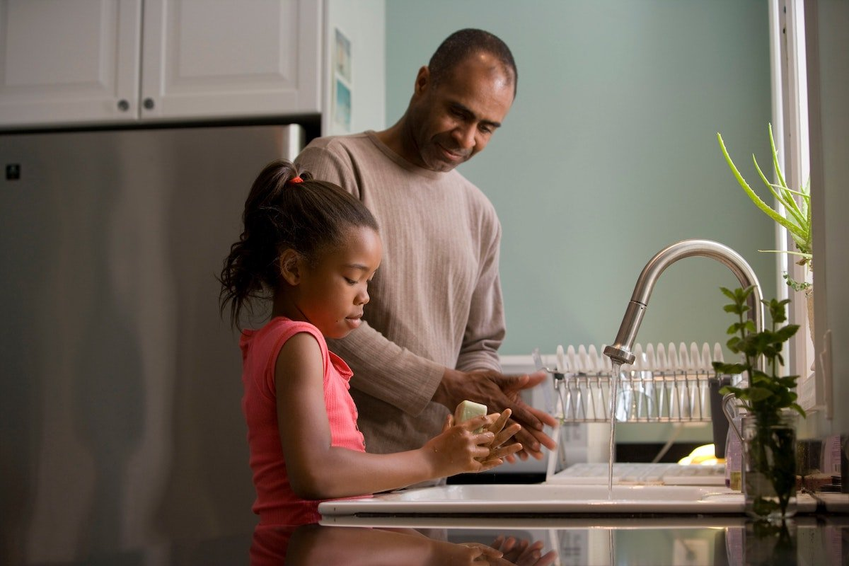 Dad with his daughter washing dishes
